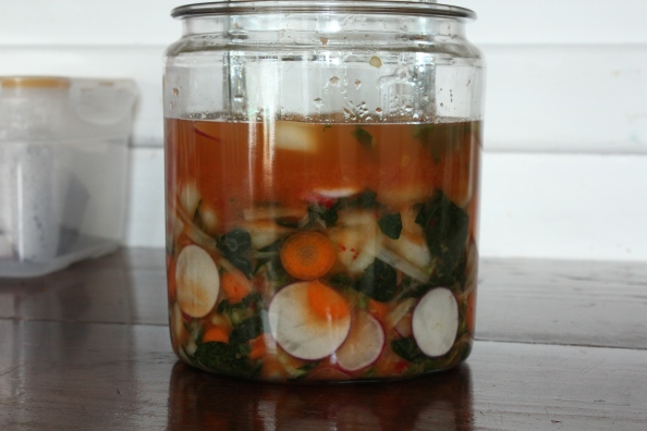 A new batch of kimchi weighted with a glass jar